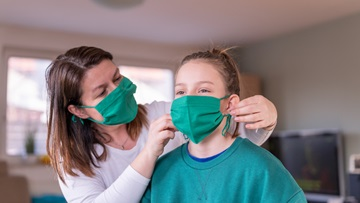 adult fitting face mask to young person