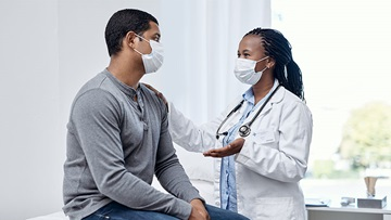 Masked doctor speaking with masked patient in clinic room