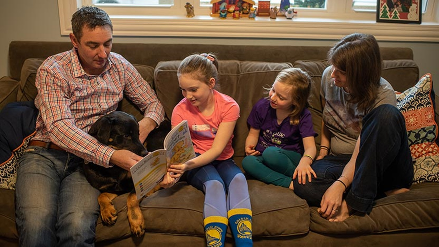 Celiac disease patient Niamh Bourke reading her favorite book with her family