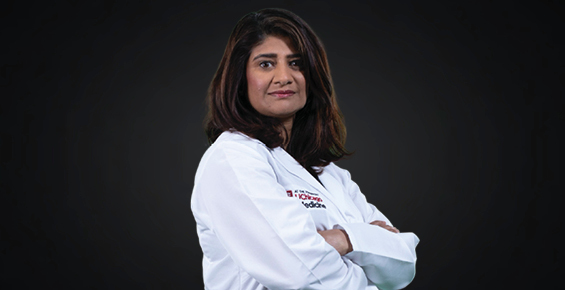 Dr. Sonali Smith in a white coat with her arms crossed facing the camera