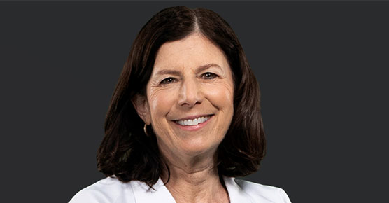 Susan Cohn, MD, in a white coat facing the camera against a black background