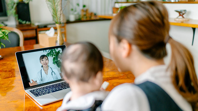 Woman holding a baby looking at a computer where she is chatting with a doctor