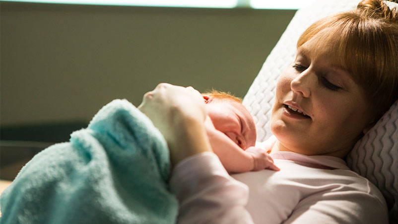 Mom cradles newborn at Family Birth Center